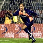 9) A semifinal da Libertadores de 2000, mais um dia de São Marcos. Tendo perdido o primeiro jogo por 4x3, o Palmeiras precisava ganhar o jogo para levar para os pênaltis. O problema é que o Corinthians de Luizão, Edílson e Marcelinho jogava mais que a gente, e só uma catástrofe tiraria a primeira final de Libertadores da história do Corinthians. Eu era um dos poucos palmeirenses que pegavam dois gomos (de 12) no Morumbi, junto com meu primo Rodrigo e a Dora. Em campo, a soberba falou mais alto, os corinthianos chegaram a trocar passes de calcanhar dentro da área e o Palmeiras conseguiu ganhar com um gol de cabeça inacreditável de Galeano. Mas o melhor ainda estava por vir: no penalti decisivo, nosso ídolo Marcos catou a bola do odiado Marcelinho carioca, transformando aquele momento em um dos mais agradáveis de todos os tempos. https://www.youtube.com/watch?v=wegDubP1s80. Peguei a foto aqui: http://imortaisdofutebol.com/2012/06/07/esquadrao-imortal-palmeiras-1998-2000/ .
