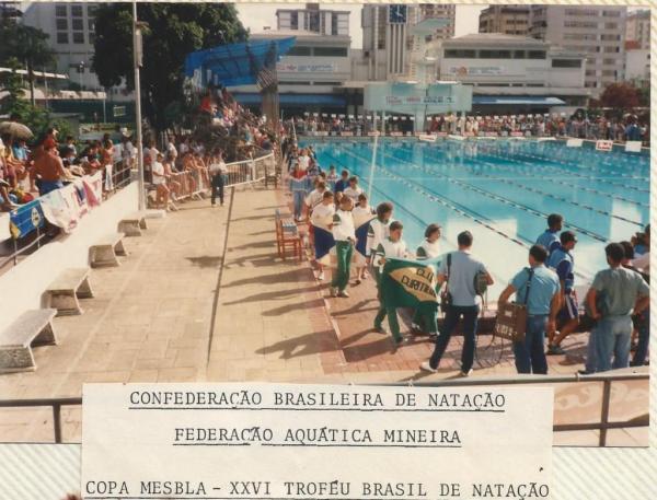 Desfile de abertura. Piscina do MTC ainda com duas profundidades e a plataforma de saltos. Isabele e Becker com a bandeira do Curitibano. Eu e Celeste logo atrás.